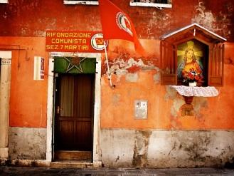 Γραφεία της Κομμουνιστικής Επανίδρυσης στη Βενετία, 2007. Στον τοίχο σφυροδρέπανα, η σημαία τουκόμματος και, λίγο παραπέρα, εικονοστάσι με τον Χριστό. Φωτογραφία του Van Velichko, από το flickr