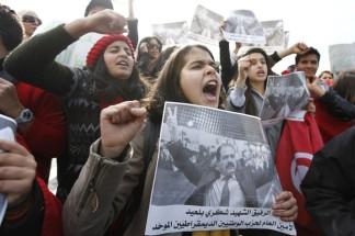 Διαδηλώτριες κρατάν αφίσα με τον δολοφονημένo ηγέτη της Αριστεράς Τσόκρι Τσόκρι Μπελαΐντ.