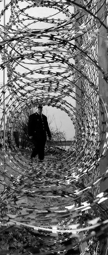 Αστυνομικός κοιτάζει μέσα από τον φράχτη, στη Νέα Βύσσα,. Πηγή,