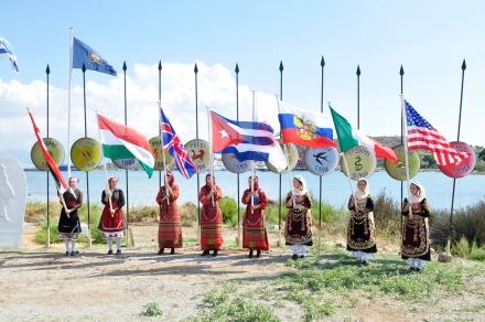 Από τον εορτασμό, 29.9.2015. Κοπέλες με παραδοσιακές ενδυμασίες υψώνουν σημαίες των συμμάχων χωρών (ΗΠΑ, Καναδάς, Ιρλανδία, Κούβα, Ουγγαρία, Ρωσία). Πηγή: ιστοσελίδα του Υπουργείου Εθνικής Άμυνας (www.mod.mil.gr)