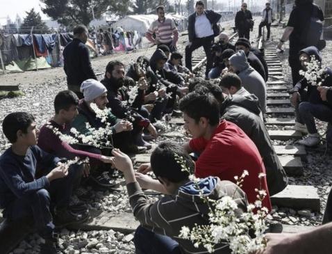 Διαμαρτυρία προσφύγων, που κάθονται στις γραμμές του τρένου, κρατώντας λουλούδια στα χέρια.Ειδομένη,,1.3.2016.Φωτογραφία EFE